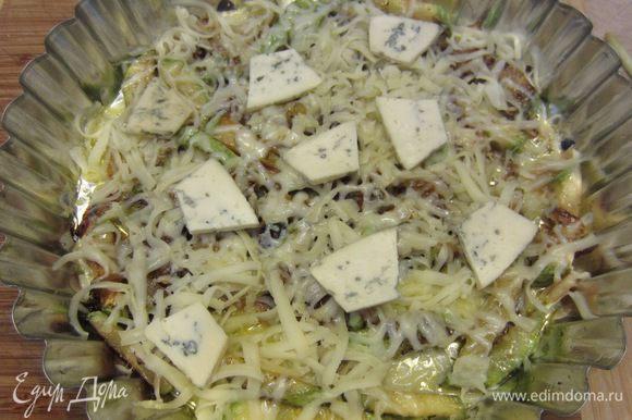 Возьмите круглую форму. Смажьте ее маслом, выложите рис в форму. Попробуйте рис - он должен быть нормально посолен. Если недостаточно - досолите. Выложите сверху кабачок с луком ровным слоем. Порежьте Дорблю и выложите кусочки сверху. Посыпьте натертым на крупной терке моцареллой.
