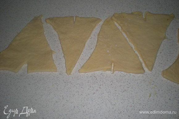 Обрезать не ровные края.Нарезать тесто на треугольники.В основании каждого треугольника нужно сделать маленький надрез,он поможет завернуть тесто в круассан.Как-то не досмотрела и видимо сильно увлеклась процессом,совсем забыла сфотографировать процесс заворачивания.Попробую описать.Берем с двух сторон за основание треугольника и начинаем заворачивать,немного растягивая в стороны от надреза.Не сжимайте сильно тесто-правильно свёрнутый круассан должен без особых усилий раскручиваться обратно.Выложить круассаны на противень(я простелила бумагой)смазать яйцом от центра к краю.Тогда излишки яичной смеси не будут склеивать тесто.