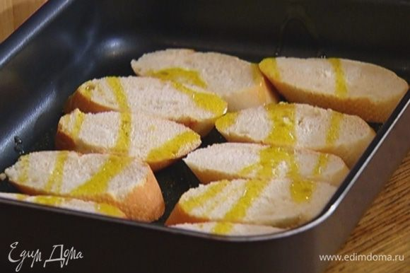 Багет нарезать ломтиками наискосок, выложить на противень, сбрызнуть оливковым маслом и отправить в разогретую духовку на 5–7 минут.