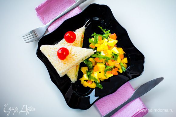 Срезаем с сэндвича корочку, режем сэндвич на треуголники, протыкаем зубочисткой и украшаем половинками помидорок черри