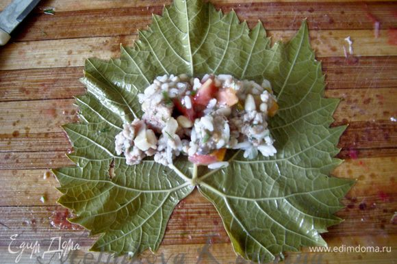 Подготовить тару для укладывания готовой долмы (казан/кастрюля с толстым дном), выстелить дно несколькими листиками. Сформировать долму. Для этого положить листик блестящей частью вниз, выложить 1 ст.л. фарша.