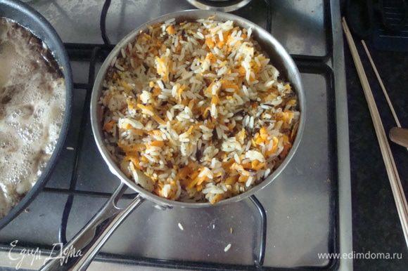 """Соединяем рис и морковь с луком. Маленькая хитрость: не рис выкладывать в сковороду к овощам, а наоборот, в кастрюлю с рисом выкладывать лук и моркову. Во-первых, меньше жиров, во-вторых, оставшийся после овощей соус мы используем для легкой обжарки курицы. Кастрюлю оставляем на несколько минут на медленном огне, в конце добавляем орегано и базилик, перемешиваем и даем """"простояться"""" на выключенной, но еще горячей плите."""