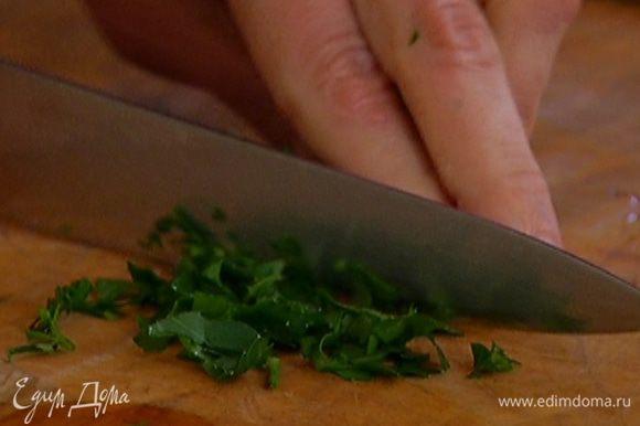 Петрушку мелко порубить и половину ее добавить в кастрюлю.