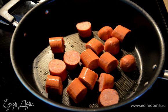 Сварить корич.рис в 4х.стаканах курин.бульона. На сковороде на олив.масле в течение 2-3мин.пожарить порезанные колбаски.