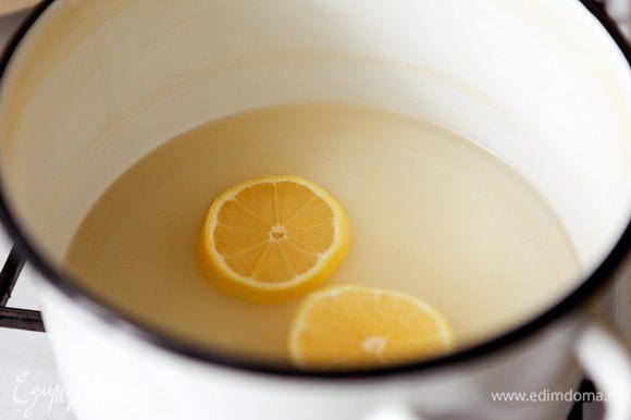 В кастрюлю налить воду, высыпать сахар и положить лимон. На сильном огне довести до кипения, затем на медленном огне дать покипеть 10 мин.