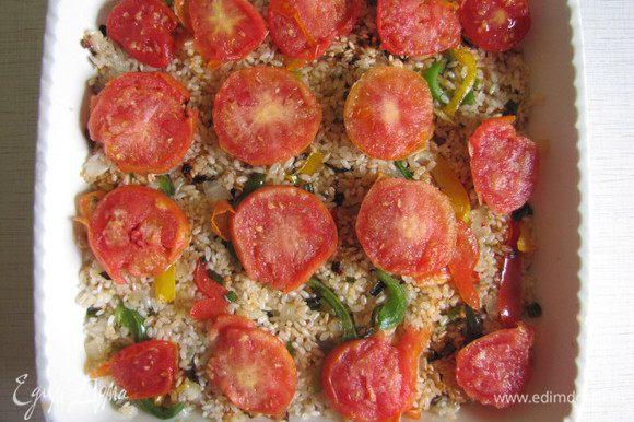 На дно огнеупорного блюда выложить порезанные кружочками помидоры, затем рисовую смесь и опять кружочки помидор. Залить стаканом воды, накрыть крышкой и поставить в предварительно разогретую духовку минут на 20. Вода должна впитаться.
