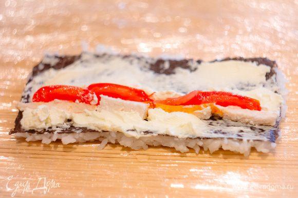 Деревянную циновку оборачиваем целофановой пленкой. Листы нори разрезаем напополам. На каждую половинку выкладываем рис, переворачиваем рисом на целофан и другую сторону довольно обильно смазываем сливочным сыром. Выкладываем ломти куриного филе, помидоры и заворачиваем