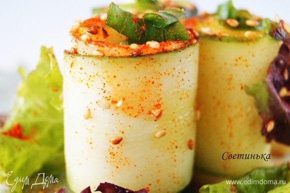 Осталось только выложить салатные листья на тарелку. На них ставим сырно-огуречные рулеты. Брызгаем на них оливковым маслом, посыпаем кунжутом и сладкой паприкой.