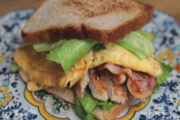 Оба куска хлеба смазать горчицей, выложить на один из них салатные листья, омлет, бекон, индейку и накрыть вторым куском.