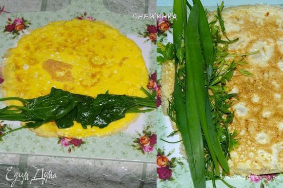 Готовый омлет снимаем со сковороды, можно на коврик для сворачивания роллов. Шпинат или зелень делим на 2 части. Одну из них раскладываем на нижней трети омлета, хвостиками в стороны.