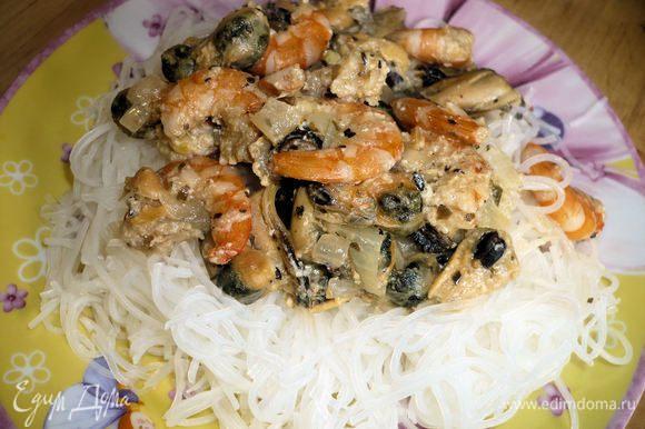На рисовую лапшу выложить морепродукты, при желании можно посыпать сверху тертым сыром