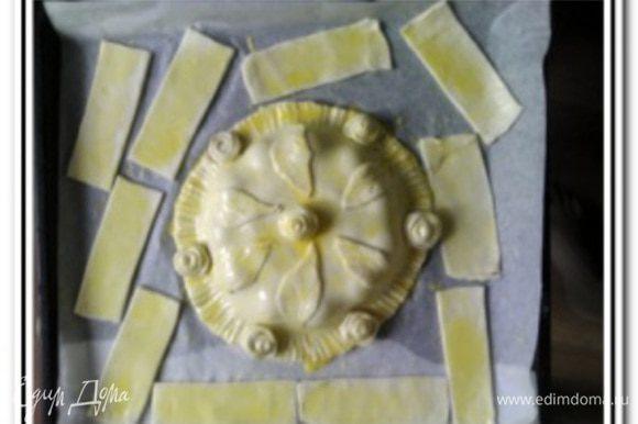 Второй пласт теста также раскатать и вырезать круг. Концы лепешки с сыром смазать водой и накрыть второй лепешкой. Пройти вилкой по основанию и украсить по собственному желанию остатками теста. Желток взбить с небольшим количеством растительного масла и смазать наш пирог.