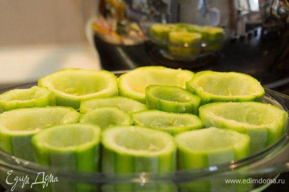 Извлечь из кабачков мякоть с помощью ножа и чайной ложки, не вынимая дно, образуя стаканчики.