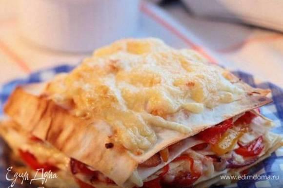 Разложить на половину кусочков лаваша начинку, присыпать сыром, добавить немного сметаны, сверху накрыть оставшимся лавашем и прогревать в духовке 3–4 минуты.