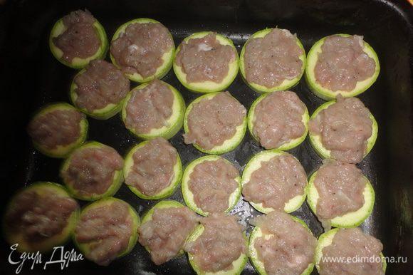 На смазанный противень выложить колечки кабачков, сверху фарш, поставить в духовку на 40 минут.
