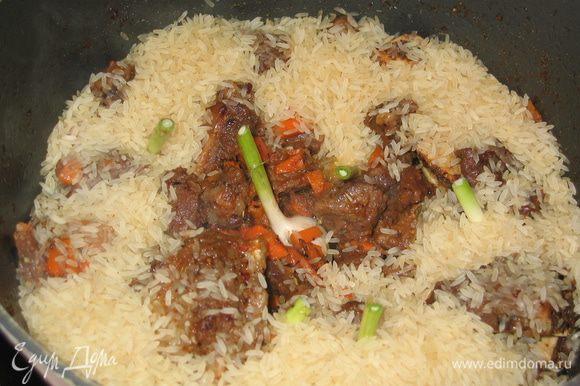 Молодой чеснок промыть и целыми головками выложить среди мяса...всыпать рис по краям казана (если использовать пропаренный рис, то предварительно замачивать его не надо...если обычный рис, то лучше его замочить в холодной воде на 1 час)
