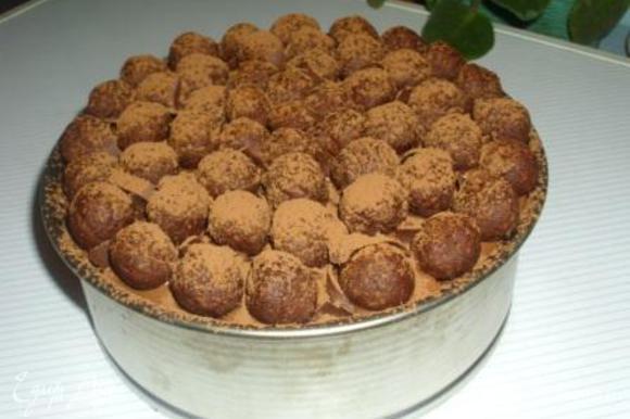 Покрыть их половиной оставшегося крема, сверху второй корж. Оставшийся крем смешать с ложкой какао и смазать им торт. Сверху выложить оставшиеся пирожные и присыпать какао.