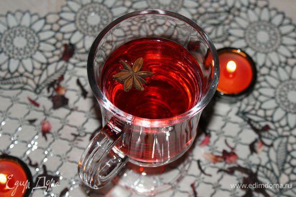 Полученный глинтвейн из каркаде процедить, соединить с медом и разлить по чашкам.