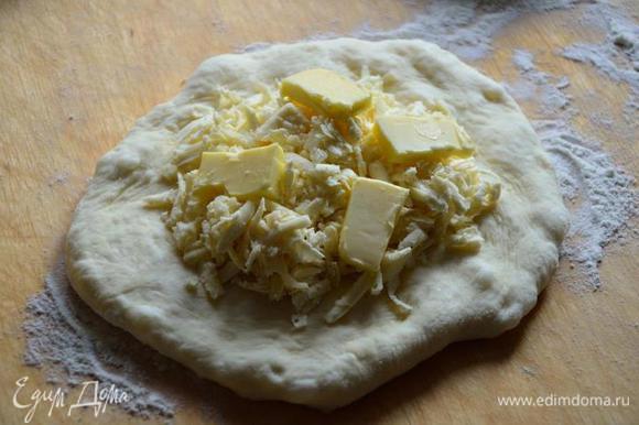 После из каждого шарика руками формируем лепешку, слегка растягивая, в середину каждой кладем тертый сыр (не жалеем) и кусочки сливочного масла..