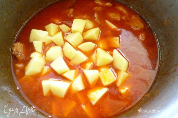 Картофель чистим и нарезаем кубиками. Отправляем в казан с почти готовым мясом, тушим 10-15 минут.