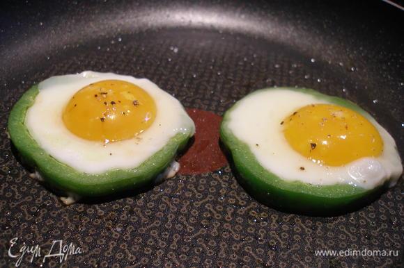 В середину перца разбиваем по яйцу. Солим, перчим. Жарим до готовности и сразу подаем.