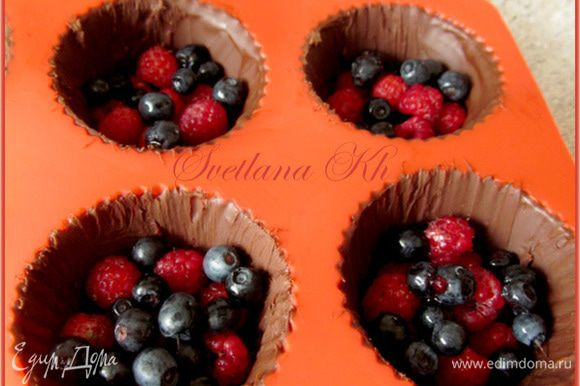 Достать шоколадные корзинки из формочек. Насыпать туда ягод, сверху - сливочный крем. Украсить ягодами и мятой.