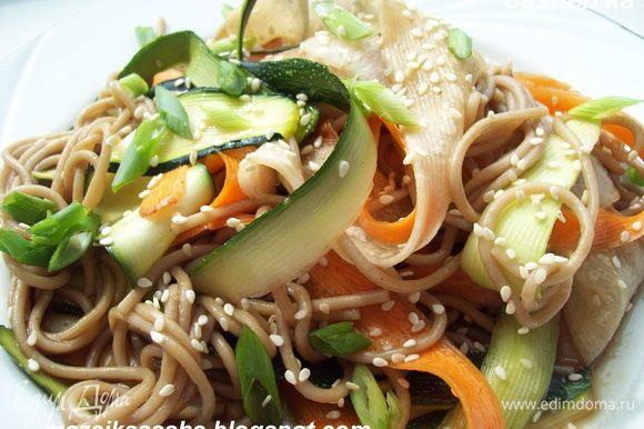 Готовую лапшу слить, перемешать с овощными лентами. Дабавить мелко нарезанный зеленый лук. Заправить соевым соусои и присыпать кунжутом.