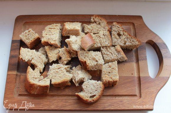Нарезать крупными кубиками хлеб и залить его мясным бульоном.