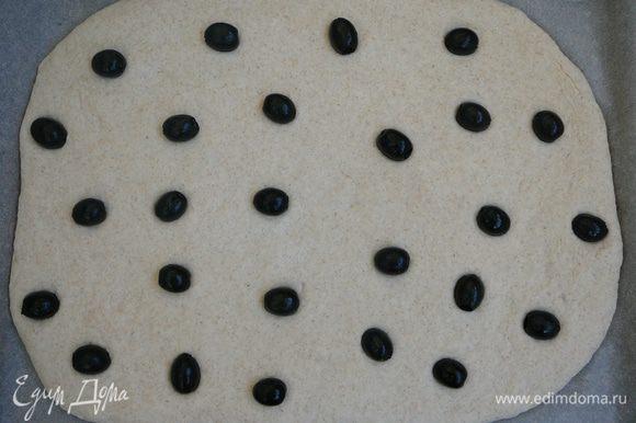 Равномерно распределить маслины, слегка притопив их в тесто.