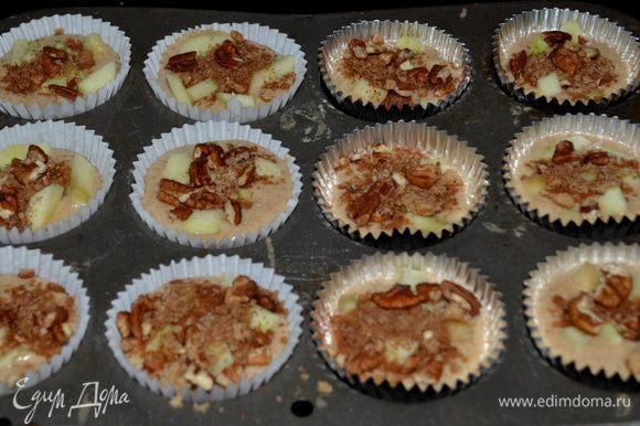 Тесто разольем по формочкам на 2/3 /при выпечке тесто поднимется/, выход примерно получается 12-16. Порезанные кусочки яблок можно смешать с тестом или разложить уже в приготовленное тесто по формочкам. Затем сверху выложить орехи с корицей и сахаром. Поставить в разогретую духовку.