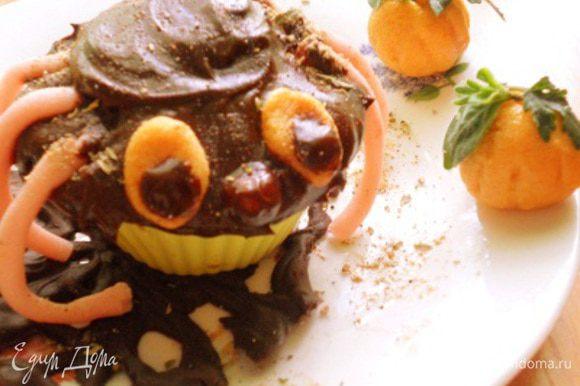 достать из духовки и остудить,украсить так:шоколад растопить с маслом и перемешать,смазать им вверх кекса,из розовой мастики сделать лапки,из оранжевой сделать глазки и носик,ножки приделать к кексу,на глазки сделать капельки из шоколада,носик обмакнуть в шоколад,все приделать к паучку,потом из оранжевой мастики сделать два шарика обратной стороной ложки сделать бороздочки так,чтобы были похожи на тыковки,сверху украсить листочками