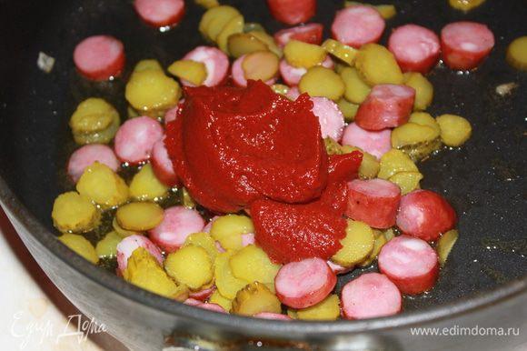 Мелко нарезать огурцы, растопить в сковороде топленое масло, положить колбаски, на сильном огне быстро прогреть их и добавить огурцы, рассол и томатную пасту.