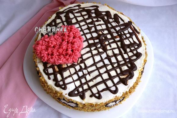 Перекладываем торт на блюдо, освободив от формы и бумаги. Для начала украсим сверху шоколадом. Берём оставшийся шоколад, растапливаем на водяной бане с молоком, хорошо размешиваем. С помощью пакетика с отрезанным кончиком рисуем волнообразные линии по верху торта.