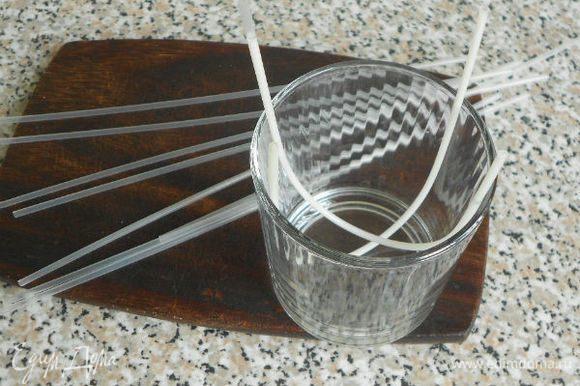 0,5 пакетика бесцветного желе развести молоком вместо воды опять же по инструкции и заполнить тонкие коктейльные трубочки (8 шт. с запасом), охладить и вытряхнуть содержимое на тарелку. Чтобы содержимое трубочек не вылилось, поместите их в стакан, изогнув. В изогнутом виде опускать на секунду в горячую воду, после чего желе легко выскальзывает из трубочки. Можно, наверное, и расплавленным белым шоколадом из кондитерского мешка украсить, но мне хотелось идеально ровных полосочек добиться, да и побоялась, что шоколад не ляжет на скользкие бока торта.