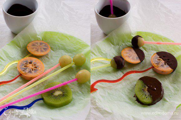 Фрукты порезать довольно толстыми ломтиками, вдеть глубоко в каждый ломтик палочку, шпажку или трубочку, застелить доску пергаментом и положить фрукты на бумагу. Отправить в морозильную камеру минимум на час. После того, как фрукты заморозятся, растопить шоколад - белый и черный, достать фрукты и окунуть их в шоколад. Киви я замораживать не стала, в порядке эксперимента решила окунать его свежим. И в результате потерпела полное фиаско - киви слетел с палочки и некрасиво шлепнулся в шоколад. Делаем выводы - предварительная заморозка обязательна