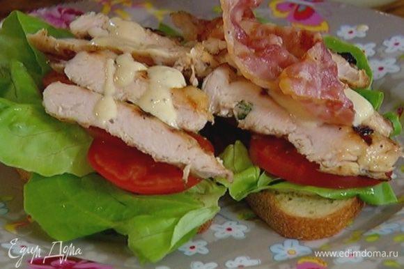 Смазать тосты частью заправки, выложить на них листья салата, кружки помидора, курицу, полить оставшейся заправкой, а сверху положить бекон.