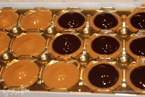 Растопить шоколад на водяной бане с добавлением 1 ст.л. сливок. Добавить сливочное масло (0,5 ст.л.), размешать. Полученную массу чайной ложкой выложить на каждую конфетку по центру