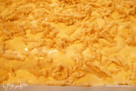 Достаем тесто из морозильника и с помощью терки распределяем его по поверхности пирога.Этот слой теста будет совсем не большим,но он предохранит творожный слой от пригорания и по румяному цвету этого тертого слоя теста легче будет определить готовность пирога.