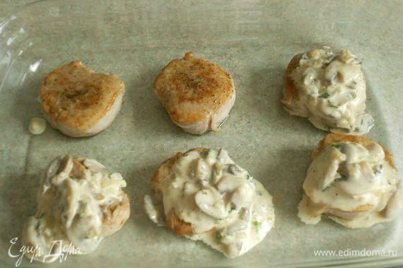 Медальоны выложить в противень, застеленный пекарской бумагой или в большое жаропрочное блюдо. На каждый положить по столовой ложке грибного соуса.