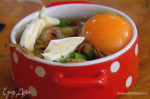 В две небольшие керамические формы выложить половину сыра, затем обжаренные грибы с беконом и луком, разбить по 1 яйцу так, чтобы желток не растекся, сверху разложить оставшийся сыр.