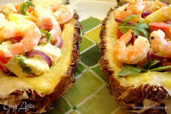 На дно ананаса выложить рукколу. Фруктово-овощную смесь заправить соусами по желанию и выложить на рукколу вместе с креветками. Приятного аппетита!