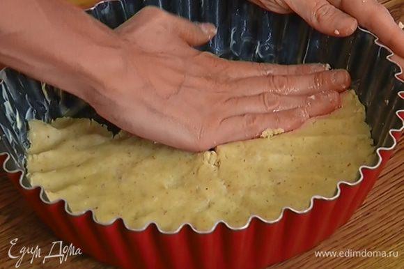 Глубокую форму смазать оставшимся сливочным маслом, выложить на дно тесто слоем в 1/2 см и отправить в морозильник на 30 минут.