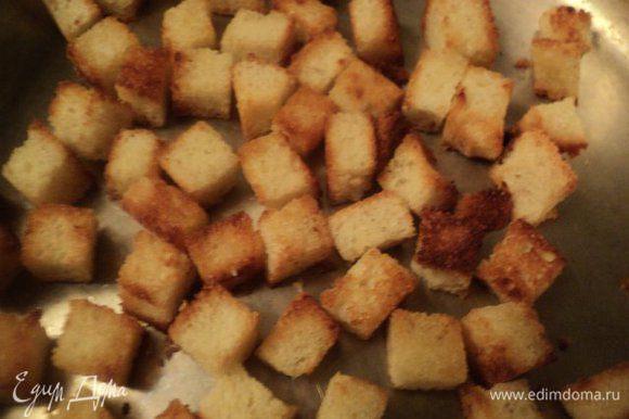 Батон обрезаем от корок и нарезаем кубиками 1х1 см. Выкладываем хлеб на противень и подсушиваем в духовке при температуре 180 градусов 5-7 мин. Мелко нарезаем чеснок и поджариваем его на оливковом масле до золотистого цвета, затем чеснок убираем и на этом ароматном масле поджариваем кубики батона до золотистого цвета.