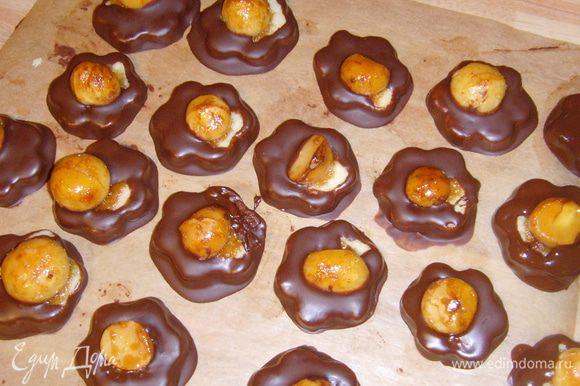 каждую печенюшку окунуть в шоколад, держа её за орех, дать лишнему стечь, поместить на пекарскую бумагу до полного высыхания.