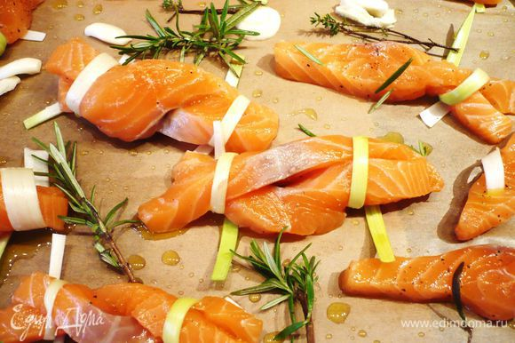 На покрытый пекарской слегка смазанной оливковым маслом бумагой противень выкладываем рыбу, кладем веточки розмарина и тимьяна, а также слегка придавленный ложкой чеснок. Сбрызгиваем оливковым маслом и выпекаем около 15 минут.