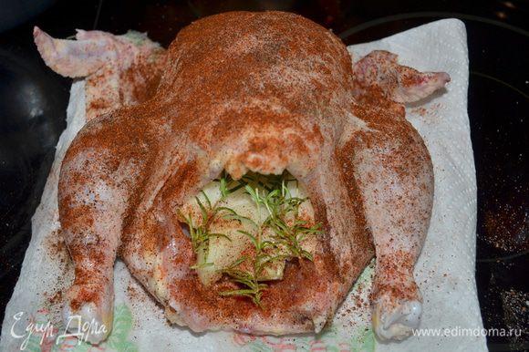 Разогреть духовку на 200 гр. Курицу помыть,просушить бумажным полотенцем.Срезать жирные места. Посыпать внутри солью и перцем. Положить во внутренность лук дольками и розмарин веточками.Обсыпать паприкой курицу.