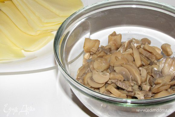 Грибы поджарить до готовности. Сыр порезать тонкими ломтиками.
