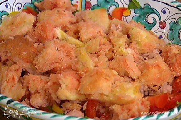В блюдо с нарезанными овощами слоями выложить половину нарезанных помидоров, затем тунец и хлеб, вымоченный в соке помидоров.