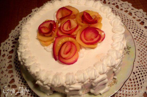 Охлажденный торт вынуть из формы. Бока и верх покрыть взбитыми сливками. Из пластинок яблок, сваренных в сиропе свернуть розочки и украсить верх торта.