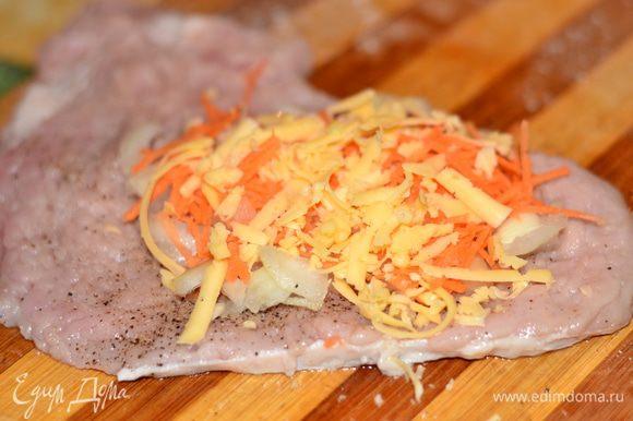 На отбитое, посоленное и приправленное мясо положить лук, морковь, сыр.